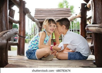 Happy two caucasian siblings sitting in a wooden house outdoors on summer day,  holding a paper boats in their hands.
