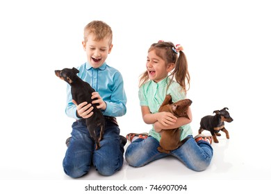 Happy two children with a dog a mini pincher isolated on a white background.