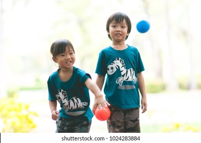 Happy Two cute asian kids playing basketball in the park with sun light background. Funny adorable Asia brother and sister playing mini ball (orange and blue color) in the garden.
