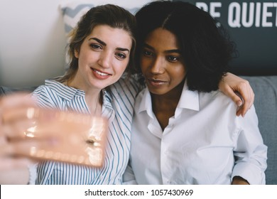 Happy two female friends making selfie photos on smartphone hugging each other.Positive caucasian model together with african american hipster girl taking pictures on telephone for publication in blog