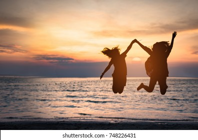 Happy two girl jumping on the beach