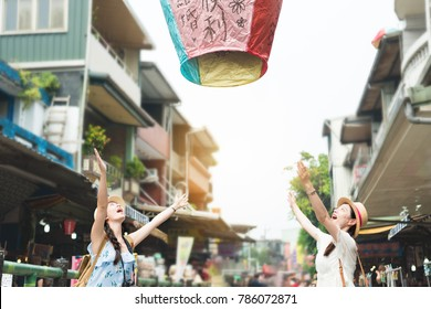 "happy two girl release let go the sky lanterns to air. Translation on sky lanterns text ""hopes of happiness and good luck in love life in the future""."
