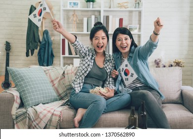 happy two girls watching soccer game on television celebrating goal and screaming cheer up raising hands with korean flag. asian women relaxing on sofa couch excited football popcorn bottle beers