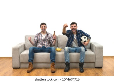 The happy two guys with a beer watch a football on the sofa