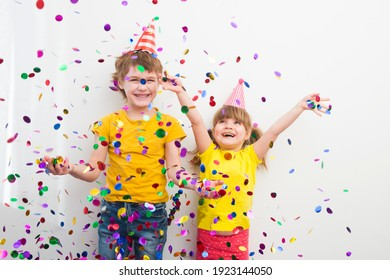 happy two kids  brother and sister with confetti on colored yellow background
