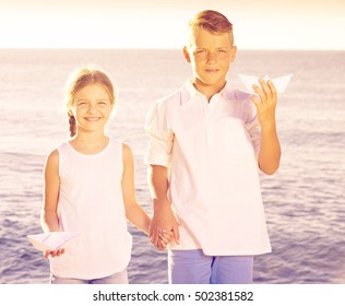happy two kids in elementary school playing with origami boat toys on beach on summer day