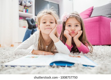 Happy Two Little girl read book, lying on floor at home, looking at camera