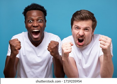 Happy two male friends in white t-shirt posing isolated on blue background. Sport leisure lifestyle concept. Cheer up support favorite team, clenching fists like winner