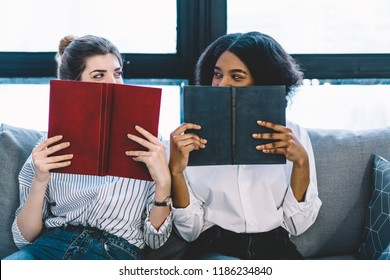 Happy two multicultural young women holding literature books in front of faces and looking at each other sitting on sofa in apartment. Positive hipster girls reading bestsellers enjoying education