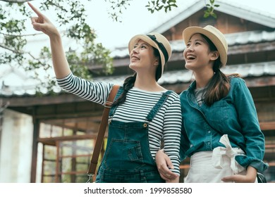 happy two young asian women friends walking outdoors standing by japanese wooden house. ladies looking aside while pointing finger to sky. cheerful female travelers smiling share beautiful scenery