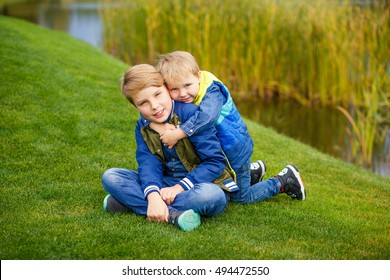 Happy two young boys sitting on the grass in a beautiful park. They hug and smile. They have blond hair and denim wear. They are brothers.