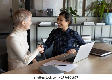 Happy two young mixed race business women shaking hands, making agreement deal in office. Smiling indian manager celebrating cooperation establishment with 30s blonde female partner at meeting.