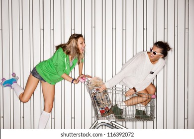 Happy two young women with shopping cart. outdoors