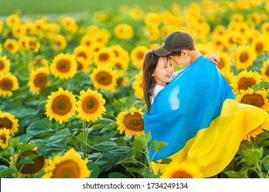 Happy Ukrainian children hug and wrap around a large Ukrainian flag against the backdrop of a sunflower field. A boy and a girl celebrate the Independence Day of Ukraine. Copy space.