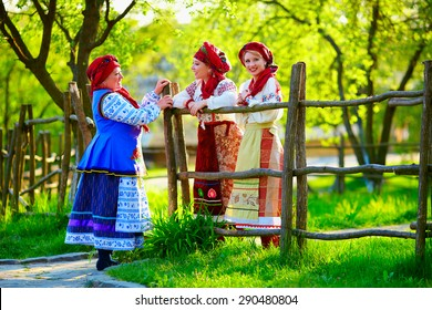 happy ukrainian women, dressed in traditional costumes, talking on the street