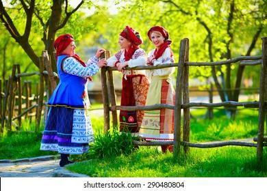 happy ukrainian women, dressed in traditional costumes, talking on the street