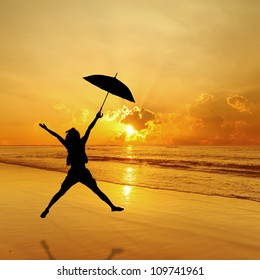 Happy umbrella Woman Jumping in beach and Sea Sunset