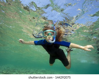 Happy underwater child in sea, beautiful healthy girl swims and having fun. Kids sport on family summer vacation. Active holiday