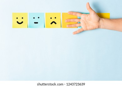 Happy unhappy and neutral mood concept. Collection of different colored sticky note papers with curled corner, open palm hand hidden three notes and empty three notes.