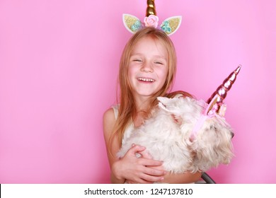 Happy Unicorn Girl with unicorn dog schnauzer. Young little beautiful blonde girl on pink background, copy space