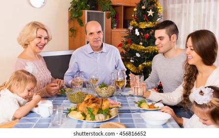 Happy united family at festive table near Christmas tree