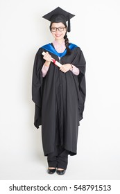 Happy university student in graduation gown and cap holding diploma certificate. Full body portrait of east  Asian female model standing on plain background.