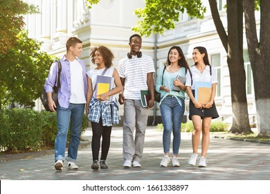 Happy university students walking together on campus, chatting and laughing outdoors during break, copy space