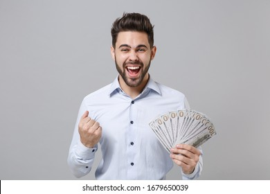 Happy unshaven business man in light shirt isolated on grey background. Achievement career wealth business concept. Mock up copy space. Hold fan of cash money in dollar banknotes doing winner gesture