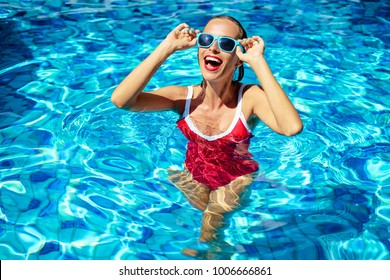 Happy vacation. Colorful portrait of young smiling woman at swimming pool.