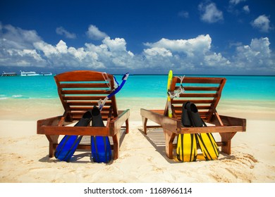 Happy vacation at Paradise. Relax on the white sand of beach. Happy sea lifestyle. Two chaise-longues with snorkeling equipment on the blue sea and cloudy sky background