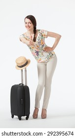 Happy vacation! Playful smiling young woman  with suitcase on white background, full length portrait