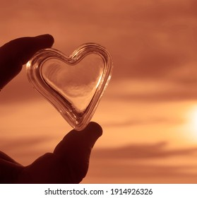 Happy Valentines Day 2021. 14th february. male  hand holding transparent white heart on sunny sky background.