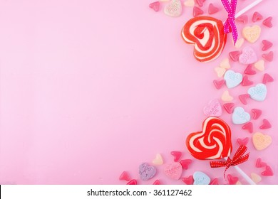 Happy Valentines Day Background with candy and red heart shape lollipops on pink wood background.