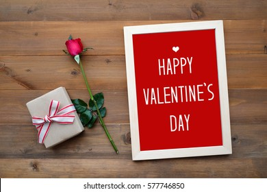 Happy valentine's day card, gift box and red rose on wood background, banner
