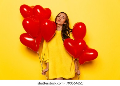 Happy Valentine's day. Cheerful girl holding red air balloons in two hands, posing at camera, giving a kiss.