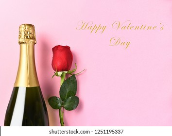 Happy Valentines Day closeup of a bottle of champagne and a single red rose against a pink background with copy space.