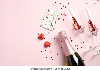 Happy Valentines day concept. Romantic dinner with champagne bottle, glasses, greeting card, heart-shaped chocolates and red confetti on pink table. Flat lay, view from above.
