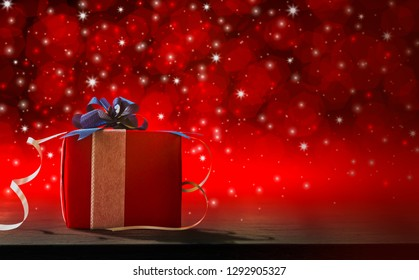 Happy valentine's Day, with gift red box on wood table and blurred bokeh and light glittering background  into darkness, concept Celebrating the festival of love