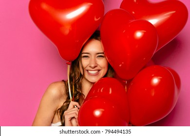 Happy Valentine's day. Gorgeous young woman, widely smiling, posing at camera with heart-shaped balloons.