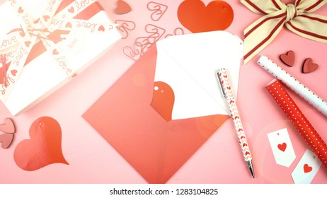 Happy Valentine's Day overhead flat lay wrapping gift and writing cards with lens flare.