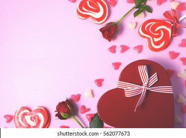 Happy Valentines Day pink background with scattered lollipops, roses and heart shaped gift, with applied retro style filters.