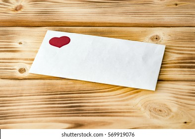 Happy Valentine's Day. Postal envelope with heart on a wooden background. Love. Celebratory background.