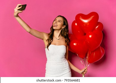 Happy Valentine's day. Smiling beautiful woman taking selfie, showing a tongue, holding heart shaped air balloons. In white dress.