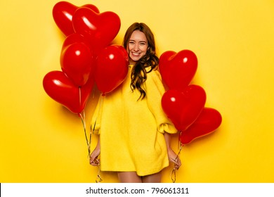 Happy Valentine's day. Smiling girl holding red air balloons in two hands, posing at camera. Dressed in yellow warm dress.