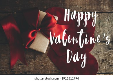 Happy Valentine's day text on stylish gift box with red ribbon and red velvet hearts on rustic wood. Love concept. Valentines day greeting card
