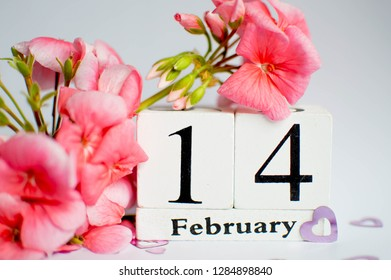 Happy Valentine's Day vintage white perpetual calendar for February 14 on a white background and a bunch of pink flowers