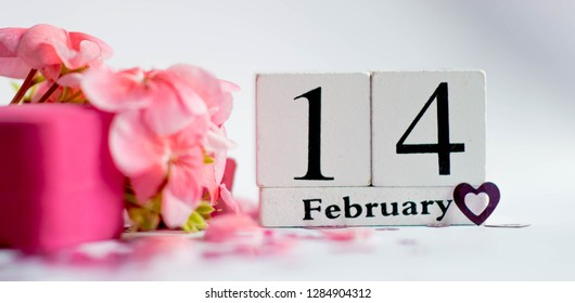 Happy Valentine's Day vintage white Perpetual calendar for February 14 on a white background and a bunch of pink flowers and a ring box for a marriage proposal
