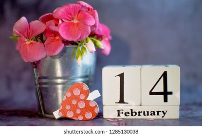 Happy Valentine's Day vintage white perpetual calendar for February 14 with a small bucket of pink flowers on a gray background and a clothespin heart