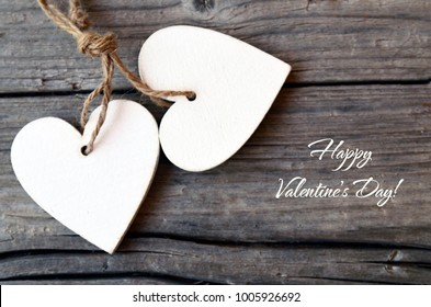Happy Valentine's Day.Decorative white wooden hearts on rustic wooden background.St Valentine's Day or Love concept.