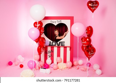 Happy Valentine's Day.heart-shaped balloons in photo booth, festive decoration.Air Balloons in the Shape of Heart. valentine's day card with beautiful woman on pink background. . Party interior